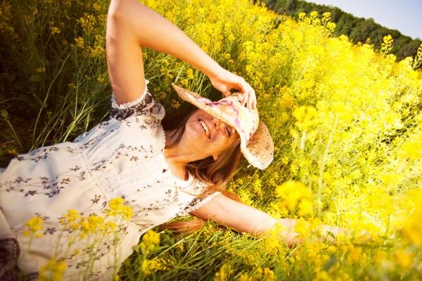 Happy woman lying among yellow wildflowers